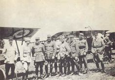 """Members of the Lafayette Escadrille pose in front of their Nieuports. From left to right: Lt. de Laage de Meux, """"Chout"""" Johnson, Victor Chapman, James McConnell, Bill Thaw, Raoul Lufbery, Kiffin Yates Rockwell, Didier Masson, """"Nimmy"""" Prince, and Bert Hall."""