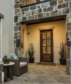 The courtyard leading to your #front #door boasts gorgeous #stone #exterior #design and a #balcony overlooking the entry. #patio #furniture