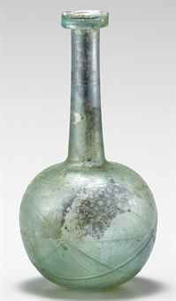 A ROMAN GLASS BOTTLE  EASTERN MEDITERRANEAN, CIRCA SECOND HALF OF THE 1ST CENTURY A.D.  Pale blue-green in color, free blown, the spherical body on a slightly kicked base, with a long tapering cylindrical neck, the collar rim folded down and up, the body with multiple wheel-cut intersecting circles, and four shallow horizontal wheel-cut grooves along the neck  7 in. (17.8 cm.) high