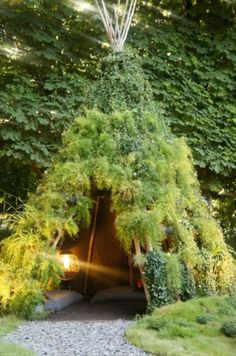 A tipi (or teepee) in the garden covered in greenery for shelter in the rain - such a fab space.