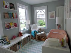 I love how calm this room feels.  Grey walls, aqua chevron rug with little pink accents. Love the book shelves too.  Very sweet baby nursery.