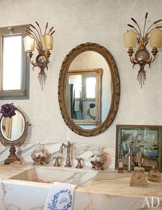 A hand-carved marble sink is surmounted by a 19th-century French mirror and heirloom 18th-century Italian sconces   archdigest.com