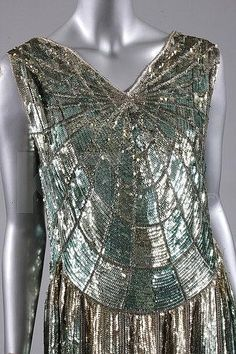 Description: A 'cobweb' sequined flapper dress, French, circa 1928, the pale green muslin ground adorned in delicate shades of green-silver sequins, with scalloped, graduated hem. Detail