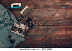 Old film camera, blue jeans and a Cassette tape on a wooden background. Top view .