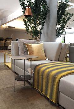 Quer uma pitada de ousadia? Aposte em algo vibrante como o amarelo ouro para pontuar almofada e outro complemento da sua sala. Veja como ficou linda essa montagem na loja de Campinas. A chaise com almofadas cinzas deixam brilhar a almofada dourada, bem como a manta nas mesmas cores. O veludo e a luminária acobreada acrescentam sofisticação.