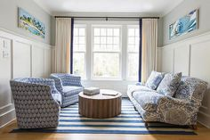 Blue living room features top part of walls painted gray and bottom part of walls clad in board and batten trim framing windows dressed in cream curtains with navy blue trim.