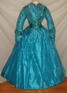 "Post Civil War, 2 piece silk dress, has separate belt that ties in back under back center peplum, trimming with blue silk fringe & satin bands, bodice lined with cotton, front hook & eye closure; skirt fully lined in cotton, some minor underarm disoloration; front wait on bodice has been altered or never finished (hidden by belt); bust: 34""; waist: 26""; skirt length: 37""; back length: 41""; hem width: 146"""