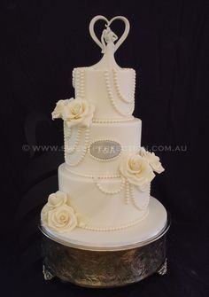 Classically elegant ivory wedding cake with edible sugar pearls, monogram and sugar roses. By Sweet Perfection.