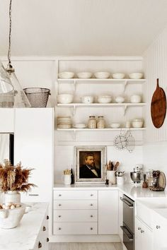 White kitchens design ideas in photos we can't stop pinning! White kitchen with farmhouse style, open shelves, white dishes, rustic decor, and charming cottage style by Kara Rosenlund.