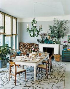 In Christopher and Suzanne Sharp's London dining room, a Kelly Wearstler rug mixes with a wrought-iron chandelier from Cairo and 19th-century farm table and chairs from Paere Dansk.