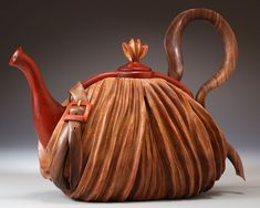 "Teapot purse! Denise Nielsen and George Worthington, handmade. ""Each twist, turn, bend and fold of our life size sculptural wood teapot/purses are carved with individually executed pieces fitted together. The body and spout are hollow, the lids are removable, the carved strap may be used as a handle. Each piece is finely sanded and oiled to celebrate the beauty, natural colors and grain of the wood."""