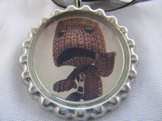 LittleBigPlanet bottle cap necklace with cord. $5.99, via Etsy.