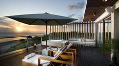 terrasse moderne en bois composite, aménagée avec deux chaises longues, parasol et canapé
