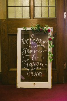 Signage on glass of an old window frame.   By creating wedding signage without too many details, this couple can now have this piece to hang in their home for years to come.   Photo: Oak & Myrrh Photography, Toronto, On