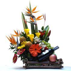 Flores exóticas, frutas y vino. Especial para cualquier ocasión. El mostrado incluye cartuchos (o calas) amarillos, gerberas, ave del paraiso y otras flores exóticas. Todo sobre una base de bambú. Flores Exóticas + Frutas + Vino (Combo Deluxe) : USD$125