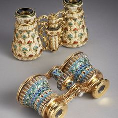 Two sumptuous pairs of opera glasses, one carved from ivory and decorated with gold and enamel by Georges Le Sache, the other gold, enamel and gem-set by Lucien Falize.