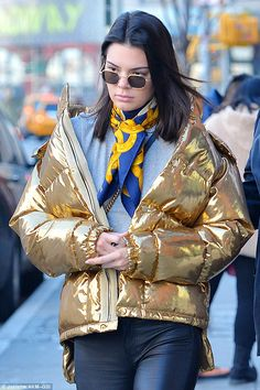 Metallic-her: The 21-year-old bundled up in a gold puffer jacket as she headed out in the Big Apple