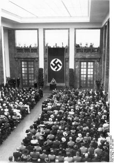 """July 18, 1937: Hitler addresses a packed house at the opening of the House of German Art in Munich. All the exhibits had been carefully vetted by the Propaganda Ministry that was broadly responsible for German Art as well. Anything not meeting the criteria of the """"New Era"""" under National Socialism was of course excluded just like anything that had been created by Jewish artists (particularly labeled as 'degenerate')."""