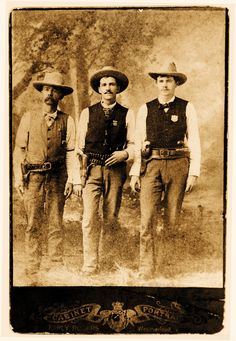 Texas Deputy U.S. Marshal Edward W. Johnson (at left) lost his right arm in an 1888 gunfight soon after this photograph was taken. He gained notoriety after an 1889 mob attacked the notorious Marlow Brothers during a jail transport, an incident that inspired the 1965 film Sons of Katie Elder. Also pictured: Texas Ranger Lorenzo K. Creekman (center) and Parker County Deputy Sheriff E.A. Hutchison (at right). – Courtesy George T. Jackson Jr. –