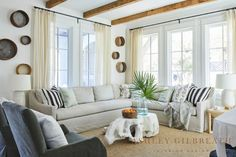 ASHLEY GILBREATH INTERIOR DESIGN: Exposed beams in this Rosemary Beach living room set the tone for the neutral color pallet. A slipcovered sectional by Verellen and a sisal rug make for easy maintenance and family-friendly living. Vintage sieves hung in groups and sheer drapery add additional texture to this space.