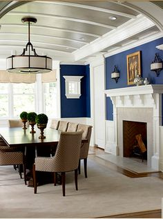 Love everything about this dining room - tin paneled ceiling, blue paneled walls, fireplace, light fixture, topiary table toppers and dining set.