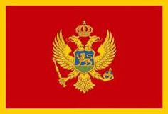 Flag of Montenegro. The flag of Montenegro is red, with the coat of arms in the middle, and golden borders. The ratio of the flag is 1:2. The coat of arms takes up 2/3 of the flag's height. The middle point of the coat of arms matches the middle point of the flag. The width of the border is 1/20 of the flag's proportions. Two versions of the Montenegrin flag are in use, horizontal, mostly used outdoor; and vertical, mostly used indoor.