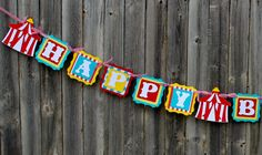 Colorful circus or carnival banner is die cut and created in alternating layers of red, yellow and turquoise. Letters are popped out to give a 3D effect. The banner is attached together with coordinat