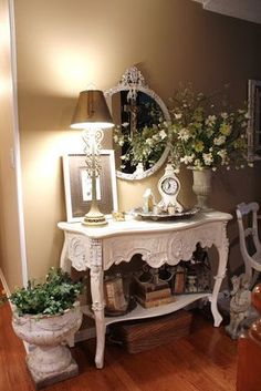 White round ornate mirror, white dresser, lamp, clock, silver tray, white urn, books, wicker basket