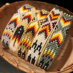 These bold cuffs were made by Navajo artist Iris Nathaniel and feature a central geometric design surrounded by feathers. The cuff was made with tiny size 15 seed beads in various colors. It me...
