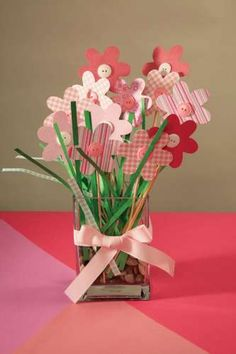 Cute Spring craft for kids using wooden skewers, a flower punch, craft paper and buttons. Would make fun Easter centerpieces too. The link is gone, but the picture is pretty self-explanatory.