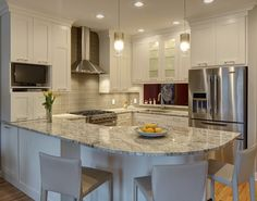 Bright kitchen design features L-shaped countertop wrapping the space, with curved bar style seating beneath the grey granite countertop. White cabinetry pairs with steel appliances and beige tile backsplash.