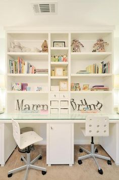 Shared girls' room features a built in white desk boasting a glass top and seating two white rolling desk chairs in front of white shelves accented with personalized name decor.