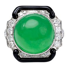 TIFFANY & CO. Jade and Enamel Ring. An Art Deco diamond ring set with a jade cabochon in scrolled black enameled borders, in platinum.Circa 1925s