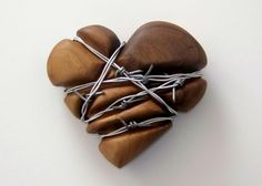 """Keep Out, I really mean it""  -  Sculpture of a carved walnut heart, with several strands of barbed wire wrapped as though they have been there a long time, and have deformed the heart."