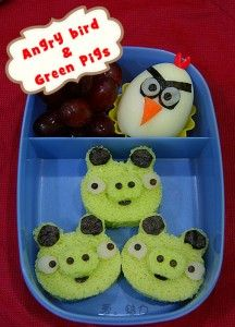 a bear cutter to cut out the pigs face from three pieces of pandan cake.  Then, used nori and crab meat (white part) to decorate the pigs.   Angry bird was made of hard-boiled egg and decorated with nori, carrot, white crab meat and a heart shape pick.  There are some grapes to filled up the bento too.