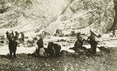 The exhausted party on the beach at Cape Valentine, Elephant Island, Aug. 15, 1916. This was the men's first experience of dry land in nearly 500 days, after an exhausting six-day boat journey. Shackleton recorded the near-hysterical reactions of the men: 'They were laughing uproariously, picking up stones and letting handfuls of pebbles trickle through their fingers like misers gloating over hoarded gold'.