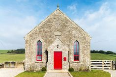 A gorgeous stone chapel turned home with a red door, green fields behind it, and blue skies