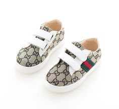 """A super cute pair of kids unisex all over """"GG"""" print logo sneakers trimmed in white faux leather. Velcro straps so easy to put on and take off. Signature red/green stripes down the side. Rubber bottom. Size 12. Brand new."""