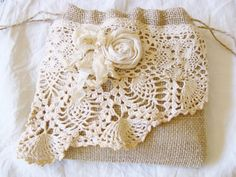 Burlap and vintage lace drawstring bag full of rustic vintage charm. Handmade from natural burlap, a piece from a vintage doily and a wide strip of vintage trim. Embellished with a rolled rose from muslin with a crinkled seam binding bow. lightweight and nice size for everyday use or lovely addition to your rustic vintage chic wedding. Measures: 7.5 x 7  Thank you for looking! Questions always welcome.