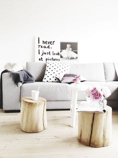 Tree stumps painted white for bedsides tables with a minimalist modern lamp
