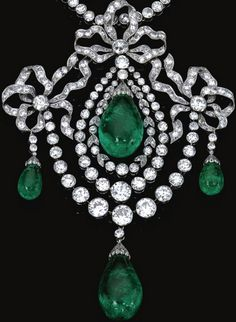 IMPORTANT EMERALD AND DIAMOND PARURE, CIRCA 1900 A pendant/devant de corsage in the Garland style, composed of three bows millegrain-set with circular- and single-cut diamonds, each suspending an emerald drop capped by rose stones, the central swing motif to a double frame of similar diamonds, embellished with a diamond set swag suspending another emerald drop.