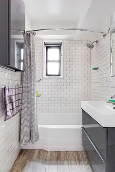 Small bathroom remodel with ikea glossy gray Godmorgon wall mounted vanity, white subway tile with dark grout, curved shower curtain bar with cute striped shower curtain