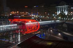 Design studio Allegory created Flux Cocoon, a red LED knot that wraps around a pedestrian bridge in Lausanne, Switzerland.