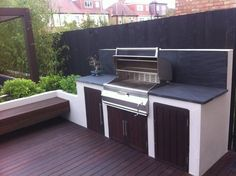 Garden in West London by Paul Newman Landscapes modern garden design with black slate paving, hardwood deck & pergola with floating bench & built in BBQ area. Tall bamboo gives screening & privacy to the boundaries. Bbq Kitchen, Backyard Kitchen, Outdoor Kitchen Design, Backyard Patio, Backyard Landscaping, Kitchen Ideas, Kitchen Designs, Backyard Privacy, Outdoor Kitchens