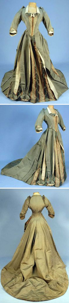 One-piece sage silk  reception gown, ca. 1888. Boned bodice with square neckline and 3/4 sleeve, cream collar, cuff, and faux vest front. Long trained skirt with asymmetrical front panel of striped brocade with floral sprays trimmed with sage bows. Stiffened lining and tapes to create fullness, hem backed with double lace ruffle. Whitaker Auctions