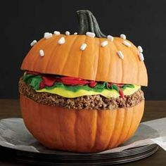 No Carve Hamburger Pumpkin: Cocoa Krispies Treats burger patty, Fruit Roll-Ups, Laffy Taffy, strawberry Sour Punch Bites and red icing condiments, Good & Plenty candies for sesame seeds on the bun.