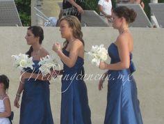 Blue bridesmaids dresses with white bouquets.
