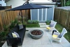 Mid Century Modern glam urban backyard with fire pit, limestone patio and shed modern patio by nebile