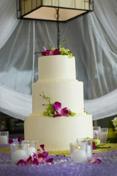 Large but simple wedding cake, made with buttercream frosting and lovely green and fuchsia flowers