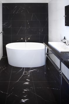 This beautiful monochrome bathroom features an ios bath. The naturally white ENGLISHCAST® material of the bath stands out against the gorgeous black tiles.